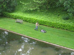 A man is mowing the lawn. Een man is aan het grasmaaien.