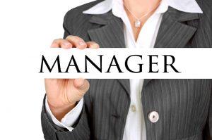 A business woman holding a sign with the word manager. To many managers can lead to diseconomies of scale. Een zakenvrouw houdt een bordje met het woord manager vast. Te veel managers kan leiden tot het tegenovergestelde van schaalvoordeel.