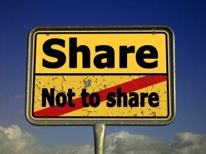A sign with the text: share, not to share. There is a red stripe through: Not to share. Een bord met: delen of niet delen. Niet delen is doorgehaald met een dikke rode streep.