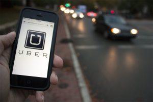 Somebody is holding a smartphone in his hand. The Uber app is opened. Sharing economy. Iemand houdt zijn smartphone vast. De app van Uber is geopend. Deeleconomie.