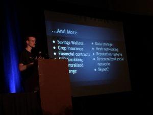 Vitalik Buterin geeft uitleg over het Ethereum Blockchain Protocol tijdens een lezing. Een conferentiescherm op de achtergrond.