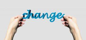 """To hands holding up the word """"change"""". Blockchain applications will change the economic system. Twee handen die het Engelse woord voor """"verandering"""" omhooghouden. Blockchaintoepassingen zullen het economische systeem gaan veranderen."""