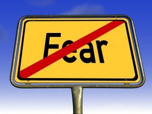 """A sign with the word """"fear"""" en a red strikethrough. Banks should not fear the blockchain technology but embrace it. Een bord met het Engelse woord voor angst. Het woord is doorgestreept met een rode streep. Banken zouden de blockchaintoepassingen juist niet moeten vrezen, maar omarmen."""