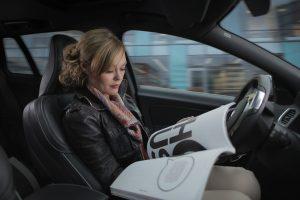 A woman is reading a magazine behind the wheel of her self driving car. Artificial intelligence will make this possible. Singularity. Een dame leest een tijdschrift achter het stuur van haar zelfrijdende auto. Kunstmatige intelligentie zal dit mogelijk maken. Singulariteit.