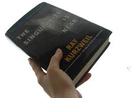 "A person holding the book of Ray Kurzweil. The title of the book is: ""The singularity is near"". Iemand houdt het boek van Ray Kurzweil vast. De titel van het boek is: ""De singulariteit is nabij""."