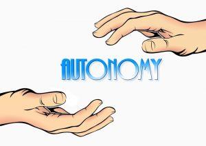 The word autonomy written in English between two hands. Het Engelse woord voor autonomie geschreven tussen twee handen.