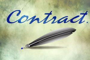 The word contract written in blue letters and a feather pencil. Smart Contracts. Het woord contract geschreven in blauwe letters en een veerpenceel. Slimme contracten.
