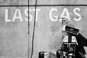 """The text """"last gas"""" written on a wall. A robot underneath. De tekst """"laatste gas"""" geschreven op een muur. Daaronder een robot."""