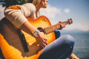 Dame bespeelt een akoestische gitaar