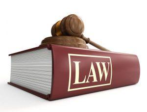 Een dik wetboek met daarin de wetgeving. Bovenop het wetboek ligt een hamer.