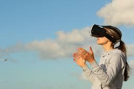 Dame met een augmented reality bril, tegen een achtergrond van een blauwe lichtbewolkte lucht.