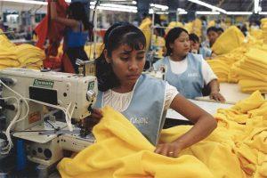 Vrouwen in kledingfabriek achter naaimachine.