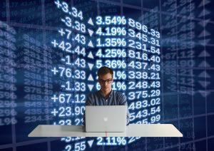 Man achter laptop, financiële derivaten, handelsbeurzen.