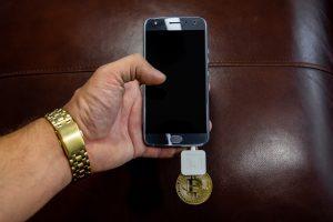 Hand, smartphone, Bitcoin.